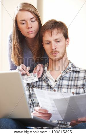 Serious Young Couple Looking At Home Finances