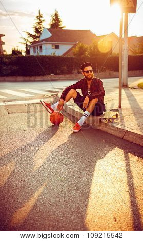 Man In Sunglasses With A Basketball And Skateboard Sitting On A City Street At Sunset Light