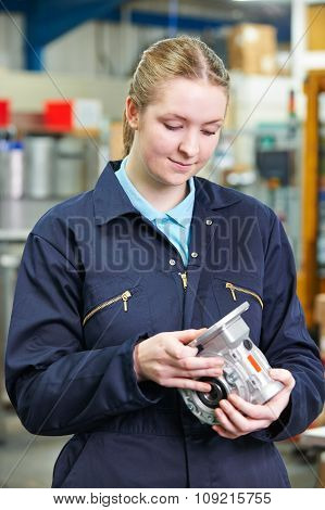 Female Apprentice Engineer Checking Component