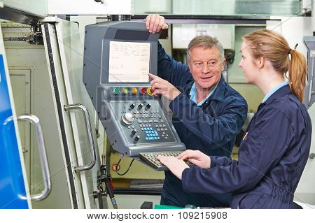 Engineer Showing Apprentice How To Use Computerized Cutting Mach