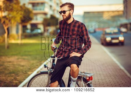 Man In Sunglasses Riding A Bike On City Street