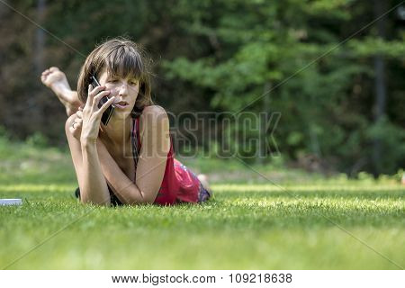 Young Brunette Lying In Green Grass As She Talks On Mobile Phone