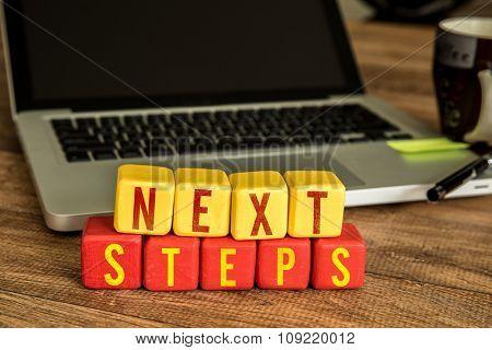 Next Steps written on a wooden cube in a office desk