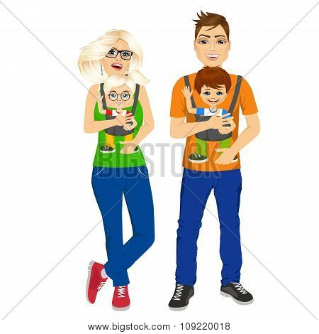 parents holding holding their children with baby carrier