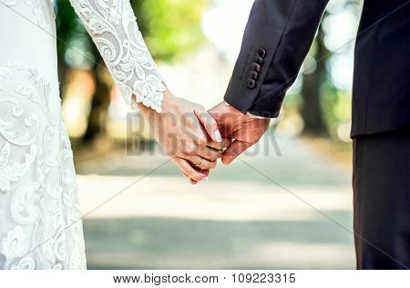 Closeup View Of Married Couple Holding Hands.