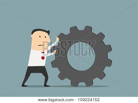 Businessman pushes a huge gear