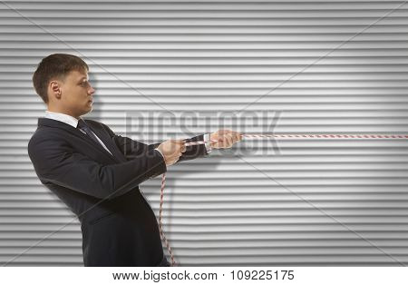 Businessman pulling a rope on wall background
