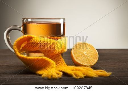 Healing glass of tea in a scarf and a lemon on a wooden background