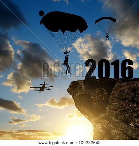 Silhouette skydiver parachutist landing in to the New Year 2016 at sunset