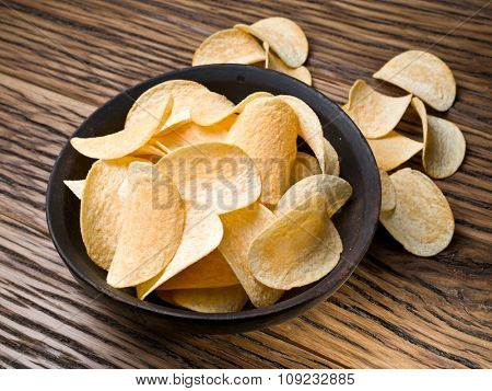 Potato chips on a wooden background.