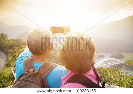 Happy Senior Couple Hiking On Mountains And Taking Selfies