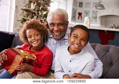 Grandfather With Grandchildren Opening Christmas Gifts