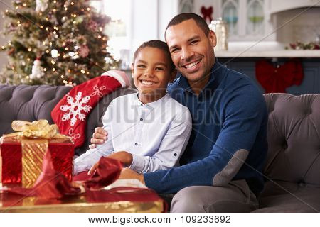 Father And Son Opening Christmas Presents At Home Together