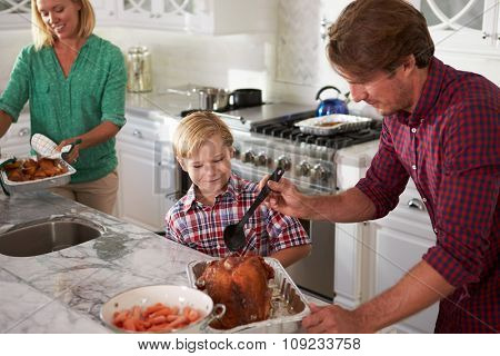 Father And Son Cooking Roast Turkey In Kitchen Together