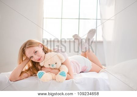 Portrait of a young pretty woman lying on the bed with teddy bear at home