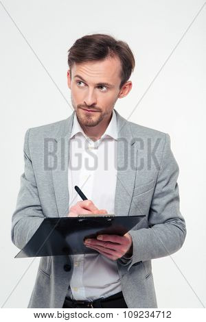 Portrait of a young businessman writing notes in clipboard isolated on a white background