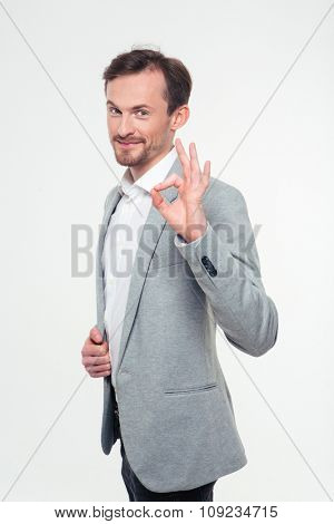 Portrait of a happy businessman showing ok sign isolated on a white background