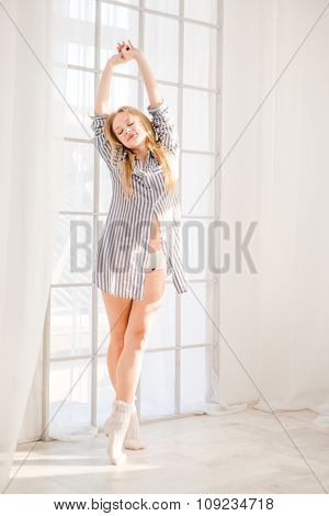 Full length portrait of cute happy content young female with long blond hair stetching near big white window