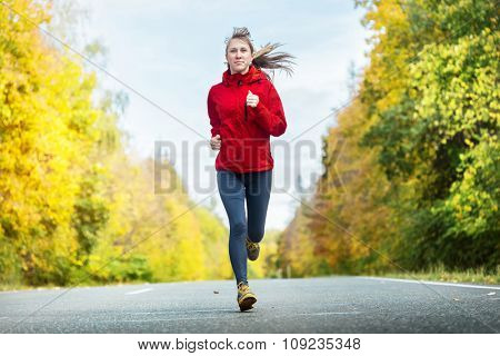 Lady running on the autumn road