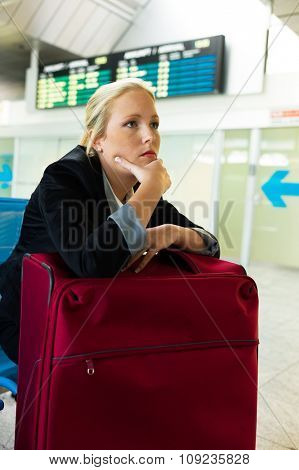 businesswoman waiting for her departure at the airport. symbolic photo for delays, flight cancellations and strikes.