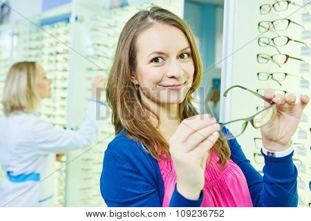 young woman choosing eye glasses in optician store