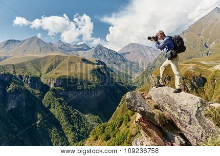 Professional photographer making landscape photos by digital mirror camera at rock mountainon