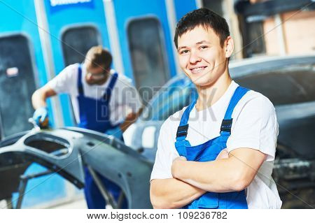 Portrait of smiling handsome auto mechanic worker holding hands folded  at automobile repair and renew service station