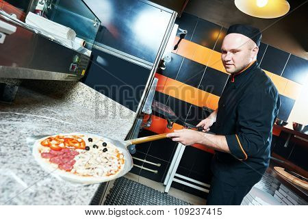 chef baker cook in black uniform putting pizza into the stove at restaurant kitchen