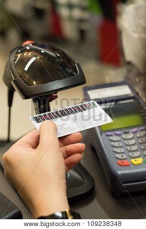 Cashier's Hand Scanning Barcode On Member Card With Credit Card Machine On The Counter