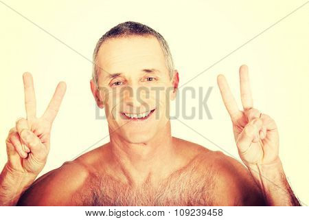 Happy mature shirtless man with victory sign.