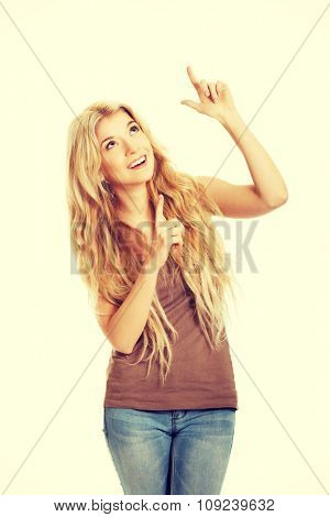 Happy student woman pointing up.