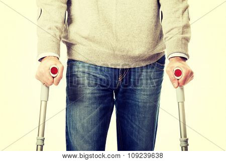 Mature male legs with crutches.