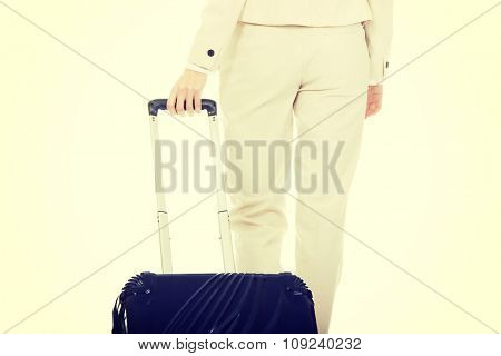 Businesswoman dragging heavy wheeled suitcase.