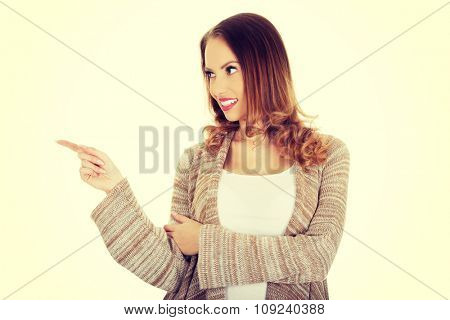 Happy smiling beautiful woman pointing aside.