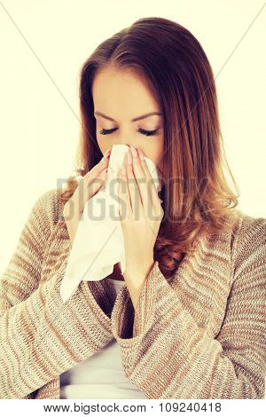 Sick woman sneezing into tissue.