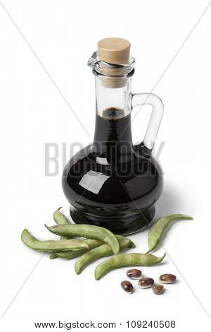 Bottle with soy sauce and fresh soybeans on white background