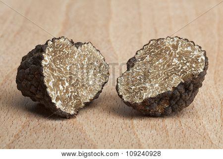 Two fresh half black truffles on wood