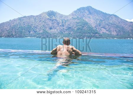 Man On The Side Of A Pool. Back View