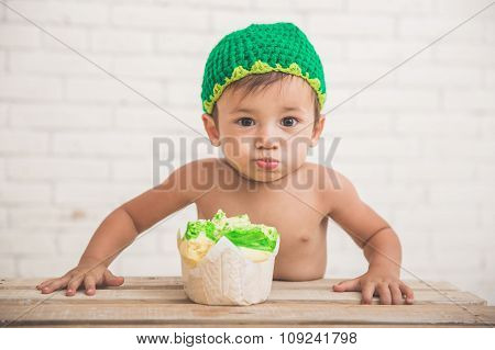 Cute Caucasian Boy Wearing A Green Knit Hat With A Bread In Front Of Him