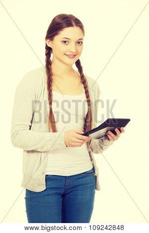 Happy teen woman hold digital calculator.