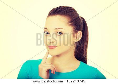 Thoughtful teenage woman touching chin.