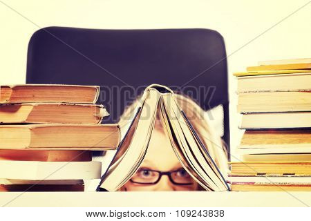 Happy teenage woman hiding behind a book