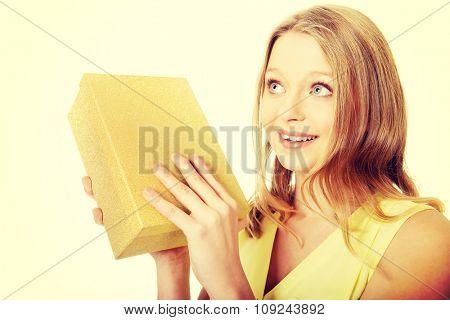 Teenage woman shaking the gift box