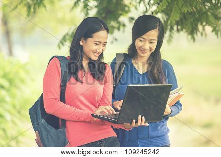 Two Young Asian Students Standing Together, One Holding A Laptop And Another Holding Books