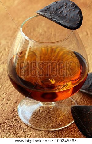 brandy glass and chocolates on a brown background