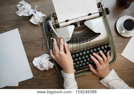 Vintage typewriter and blank sheet of paper, human hands