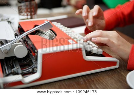 woman at table typing on old red typewriter