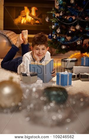 Happy young boy lying by christmas tree, reading book, smiling, looking at camera.