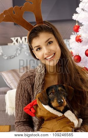 Happy woman in reindeer antler holding dog, smiling at christmas.