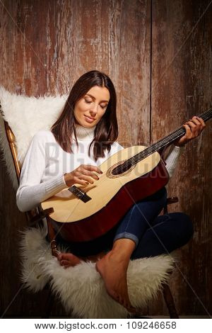 Attractive young woman playing guitar eyes closed, sitting in armchair over antique wood wall.